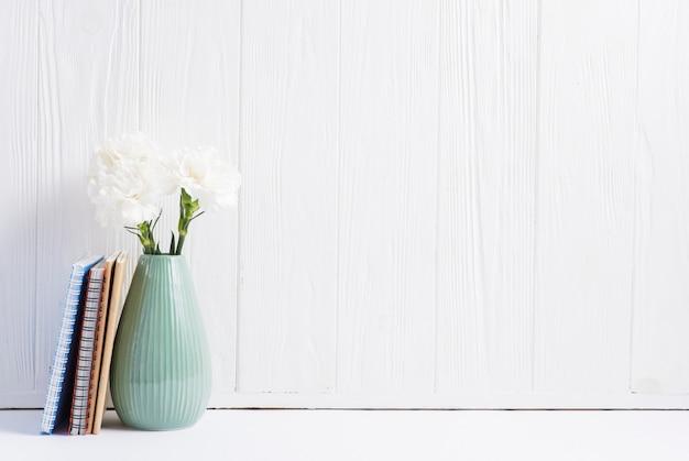 Livros perto das flores frescas no vaso contra papel de parede pintado de madeira branca