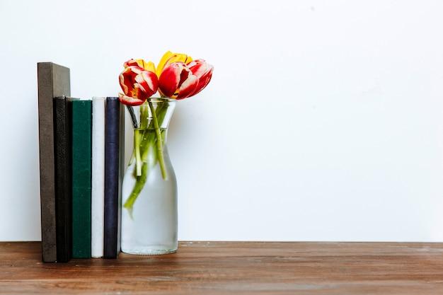 Livros perto de vaso com flores