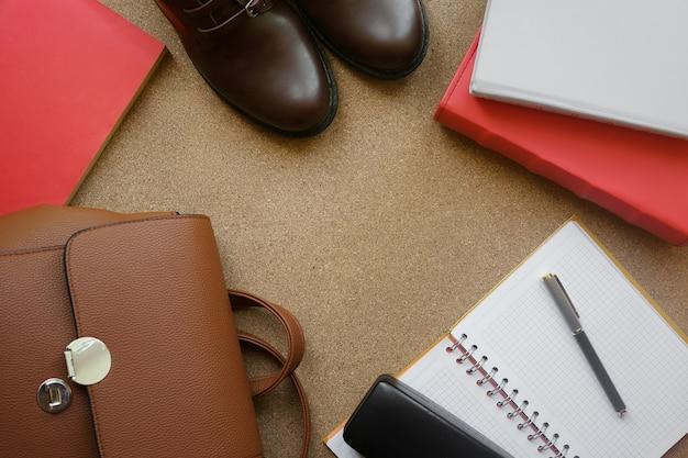 Livros planos leigos, mochila, caderno, botas, caneta no fundo da placa de cortiça.