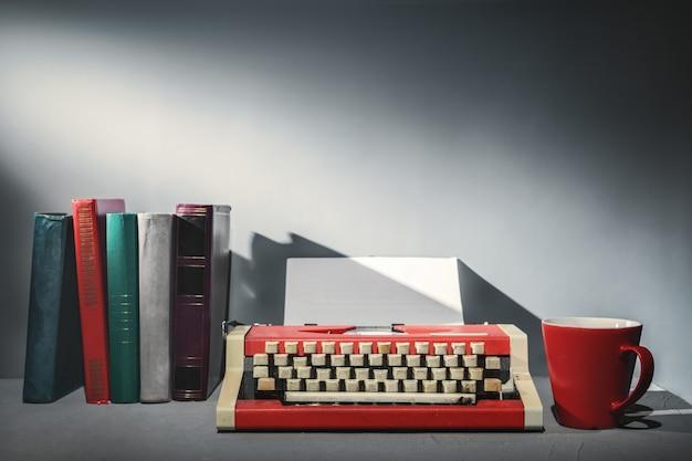 Livros, uma máquina de escrever e uma xícara de chá.