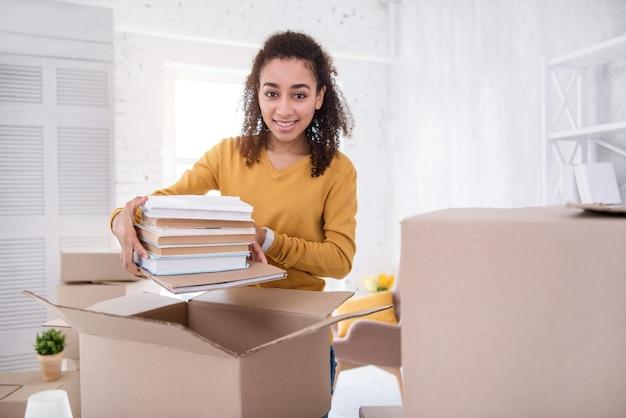 Livros úteis. linda garota de cabelos encaracolados posando para a câmera e sorrindo enquanto empacota uma pilha de livros em uma caixa