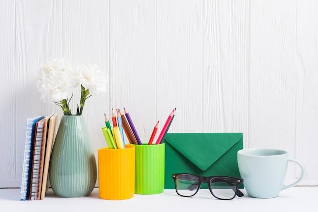 Livros; vaso; placeholder; envelope; óculos e copo de cerâmica contra o pano de fundo de madeira