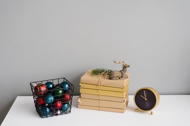 Livros, veado de brinquedo de natal, cesta de metal com bolas coloridas de árvore de natal e relógio de mesa em uma prateleira branca