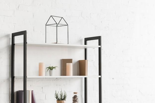 Livros, vela e planta de casa na prateleira de madeira contra a parede branca