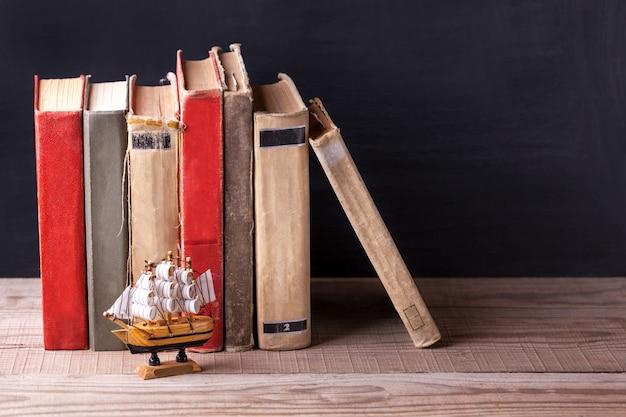 Livros velhos do vintage que estão em seguido na estante de madeira.