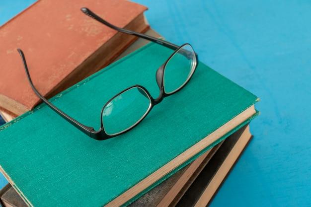 Livros velhos e vidros pretos em um azul esverdeado de madeira.