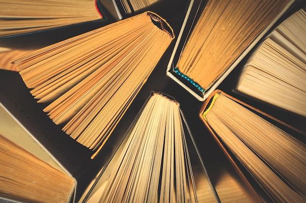 Livros velhos ou usados do livro encadernado ou livros de texto vistos de cima de.