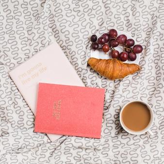 Livros; xícara de chá; croissant e uvas vermelhas na placa sobre a toalha de mesa