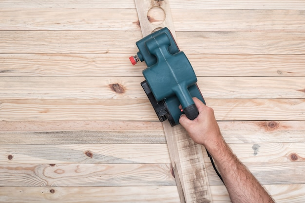 Lixadeira elétrica, lixadeira na mão masculina. processamento da peça na mesa de madeira marrom clara.