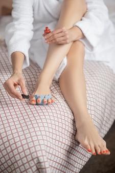 Lixador de unha. mulher de manto branco sentada na cama pintando suavemente as unhas dos pés com verniz vermelho, sem rosto