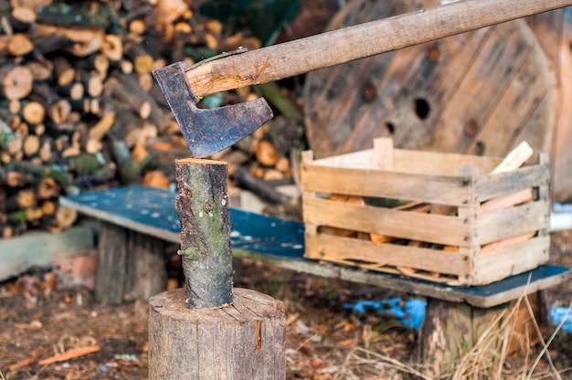 Lixão forte que corta madeira, as moscas se separam. machado, machado, machado. dividir um log com um machado. lenço de bétula em segundo plano. papel de parede de madeira