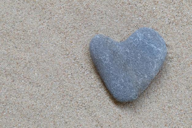 Lixe a pedra da forma do coração que descansa na areia e tenha o espaço da cópia.