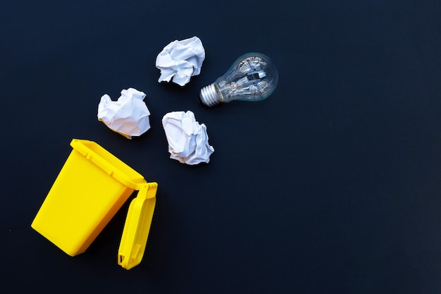 Lixeira amarela com lâmpada e papel branco amassado na parede escura. idéias e conceito de pensamento criativo. vista do topo