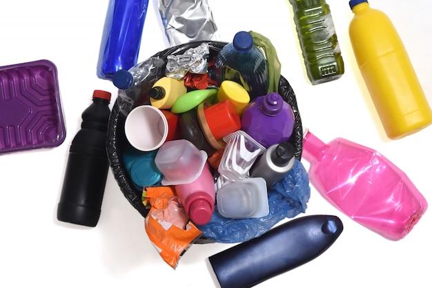 Lixeira cheia de plásticos, como garrafas, sacos ...