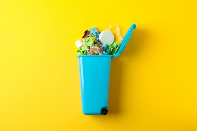 Lixeira com lixo em fundo amarelo, espaço para texto