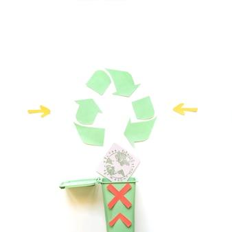 Lixeira cruzada com globo perto de símbolo de reciclagem