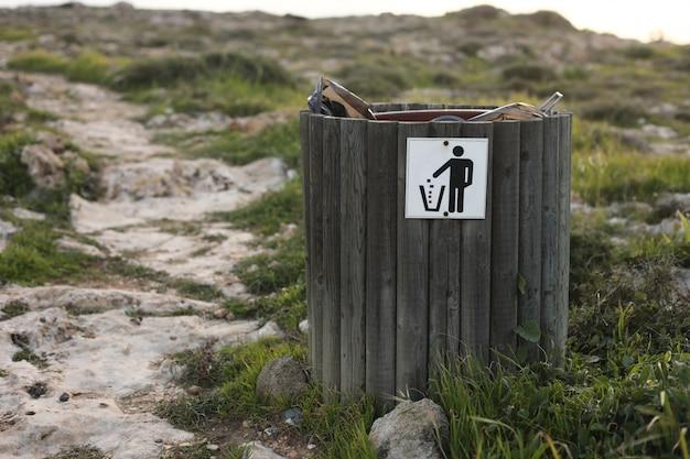 Lixeira de madeira ou lixeira com garrafa, lata de cerveja e resíduos orgânicos visíveis mostrando poluição nas áreas costeiras perto do mar