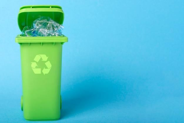 Lixeira verde com resíduos de plástico e ícone de reciclagem em um fundo azul com lugar para texto