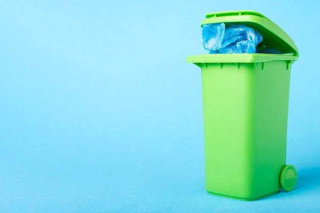 Lixeira verde com resíduos de polietileno, sobre um fundo azul com lugar para texto