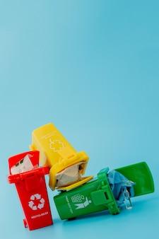 Lixeiras amarelas, verdes e vermelhas com o símbolo de reciclagem sobre fundo azul. mantenha a cidade arrumada, deixa o símbolo de reciclagem. conceito de proteção da natureza.