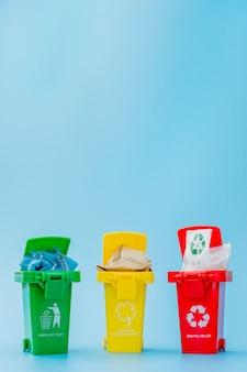 Lixeiras amarelas, verdes e vermelhas com recicl o símbolo no fundo azul. mantenha a cidade arrumada. deixa o símbolo de reciclagem. conceito de proteção da natureza
