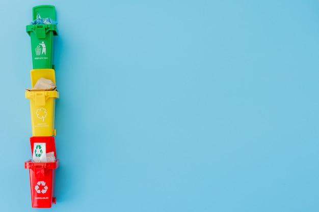 Lixeiras amarelas, verdes e vermelhas com recicl o símbolo no fundo azul.