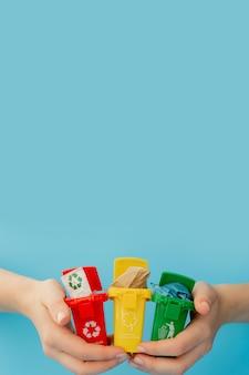 Lixeiras amarelas, verdes e vermelhas com símbolo de reciclagem na superfície azul. mantenha a cidade arrumada. deixa o símbolo de reciclagem. conceito de proteção da natureza