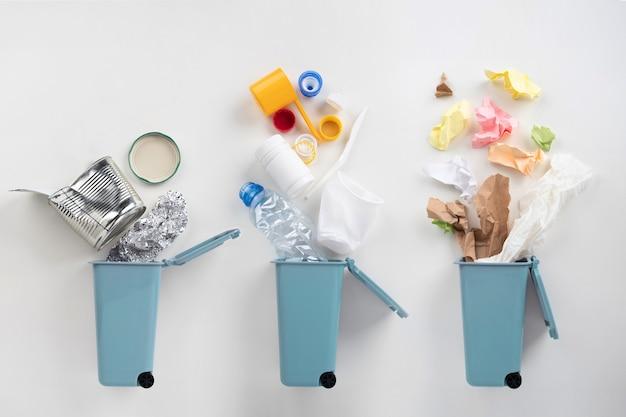 Lixeiras azuis e lixo variado em fundo cinza. conceito de reciclagem
