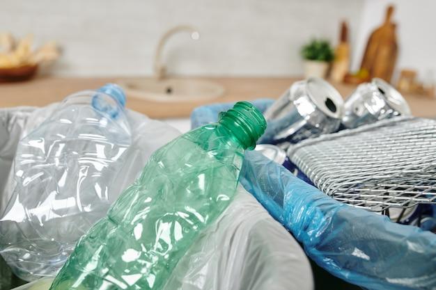 Lixeiras com latas vazias, garrafas plásticas e outros resíduos no ambiente doméstico