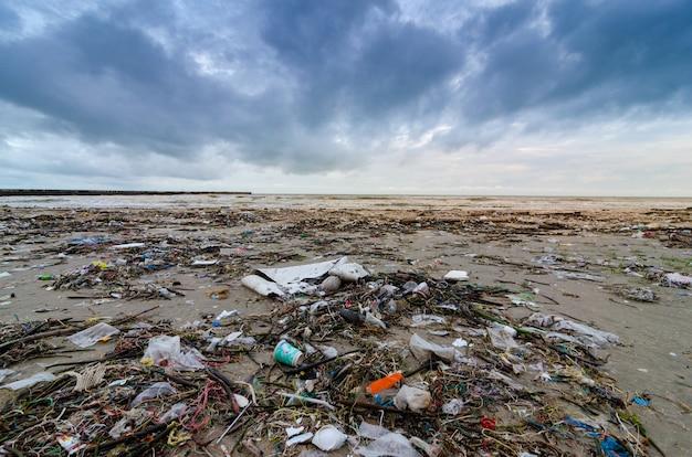 Lixo a garrafa de plástico de praia mar situa-se na praia e polui o mar