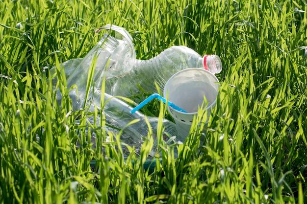Lixo, close-up de plástico em um fundo de grama verde, problemas, proteção da ecologia e do meio ambiente