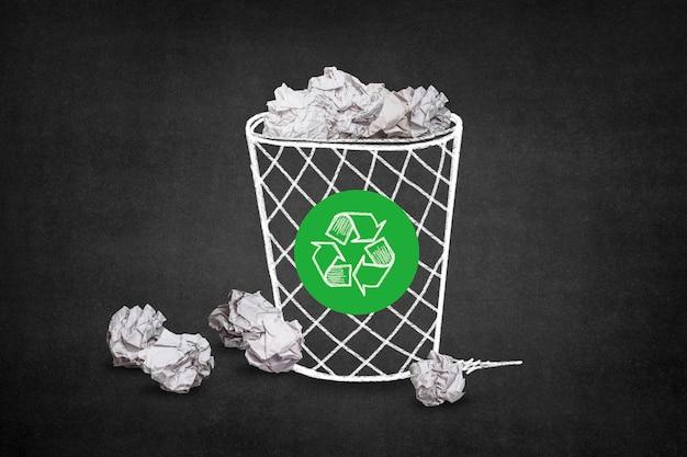 Lixo com bolas de papel e um símbolo de reciclagem