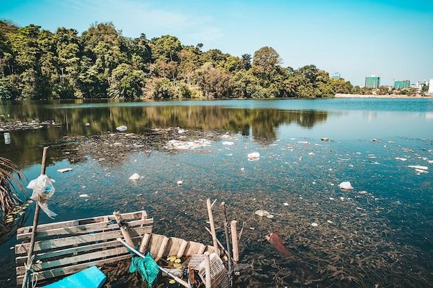 Lixo da cidade na lagoa do parque. o lixo encontra-se na água em uma das paisagens urbanas. garrafas de plástico foram jogadas na água.
