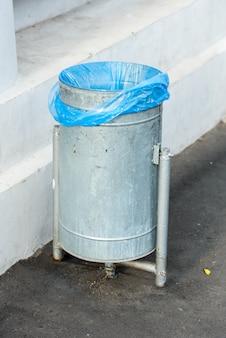 Lixo de metal de rua com um pacote