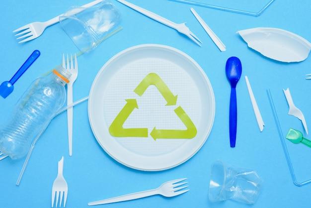 Lixo de plástico diferente e sinal de reciclagem de lixo em vista superior de fundo colorido