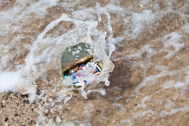 Lixo de plástico e lata foram arrastados pela onda do mar. foco seletivo. poluição ambiental por resíduos plásticos descartáveis. microplásticos no oceano mundial.
