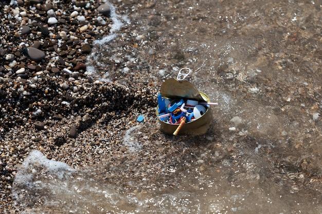 Lixo de plástico e lata na praia. lixo doméstico e lixo plástico descartável na praia. onda do mar, microplásticos no oceano mundial.