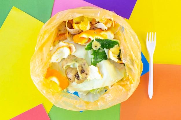 Lixo, desperdício de alimentos em um saco de plástico, sobre um fundo abstrato colorido. ecologia e poluição do planeta terra. classificação de lixo.