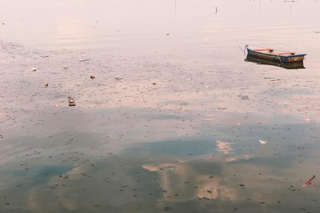 Lixo e lixo que flutuam na superfície com o navio velho dispersado.