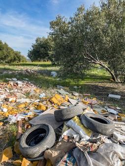 Lixo e materiais usados despejados na floresta, contaminando uma área limpa.