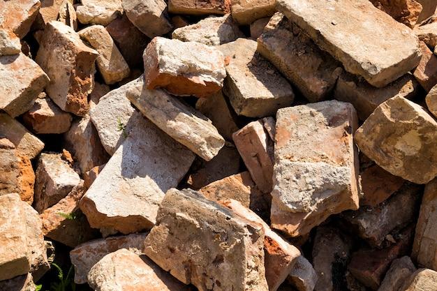 Lixo e uma pilha de tijolos vermelhos perto das ruínas de um antigo castelo ou fortaleza, um prédio abandonado