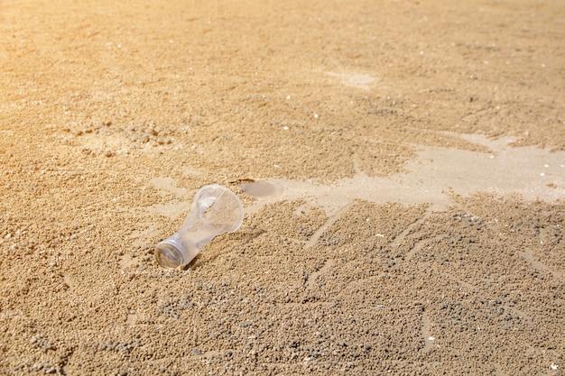 Lixo na areia da praia, mostrando o problema de poluição ambiental