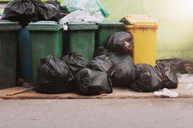 Lixo no lixo com bolsa preta no parque