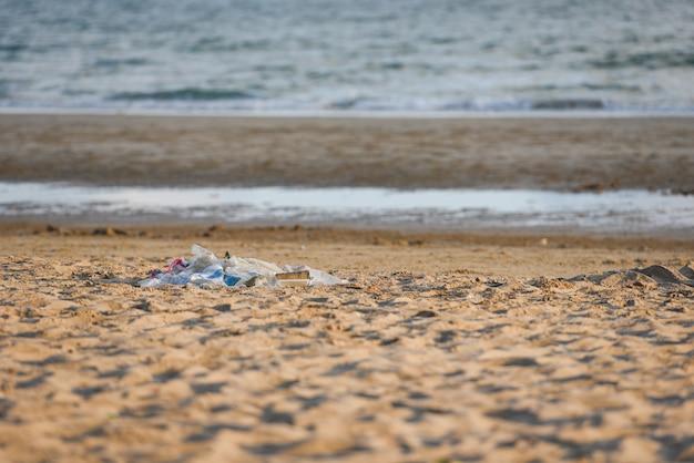 Lixo no mar com saco de garrafa de plástico e outro lixo praia arenosa suja mar na ilha