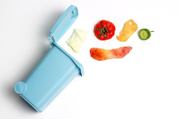 Lixo orgânico e lata de lixo em superfície plana e branca