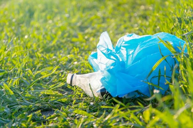 Lixo plástico em um fundo de relva verde