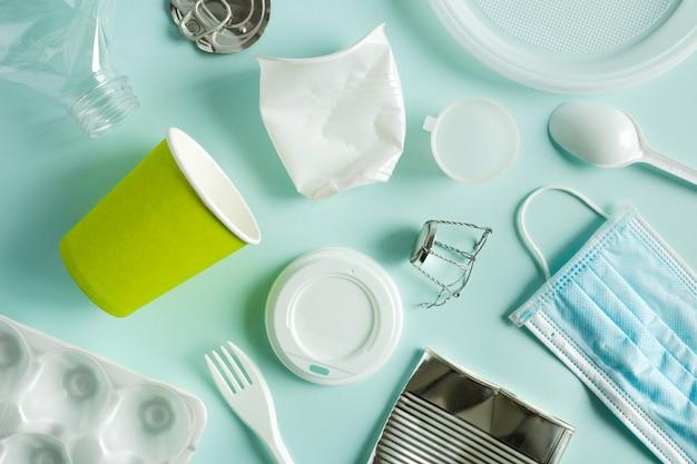 Lixo reciclado de diversos materiais, plástico, metal e outros para reciclagem. classificação de lixo. posição plana, vista superior sobre o fundo azul.