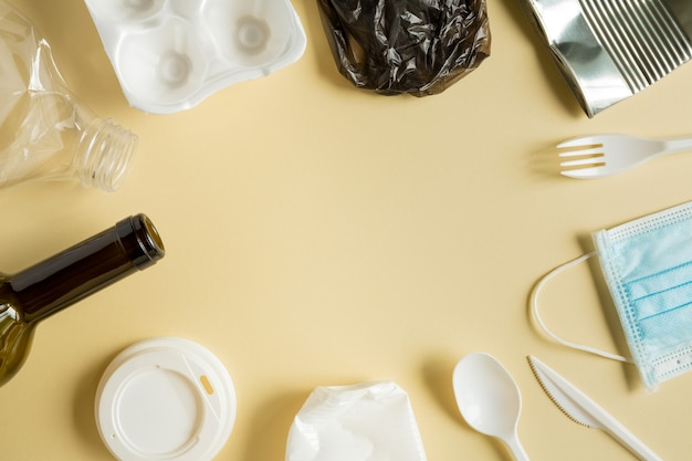 Lixo reciclado diferente de metal, plástico e outro no fundo amarelo. quadro, lugar para texto, disposição plana.