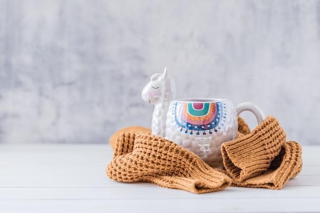 Llama colorido em forma de caneca com pulôver de malha na mesa de madeira branca