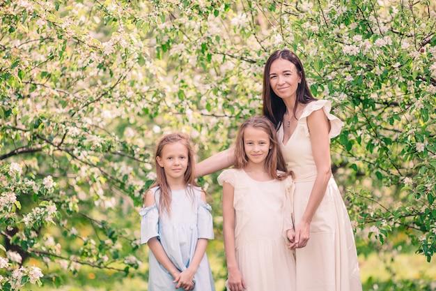 Llittle meninas com jovem mãe no jardim de cerejeira desabrocham no lindo dia de primavera